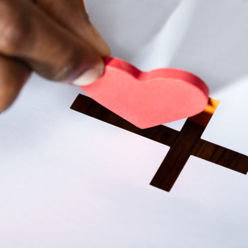 Close-up Of A Man's Hand Inserting Red Heart Shape In Crucifix Slot